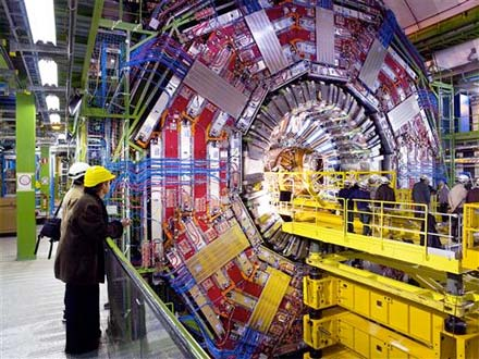 Engineers stand on a raised platform inserting the tracker into into the heart of the CMS detector. The detector looks enormous next to the people.